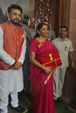 Indian Finance Minister Nirmala Sitharaman, center, and junior Finance Minister Anurag Thakur, left, stands for the media at the parliament house before presenting the annual federal budget in New Delhi, India, Friday, July 5, 2019. India's government says the economy is expected to grow at 7% in 2019-20, up from a five-year low of 6.8% in the past year. (AP Photo/Manish Swarup)