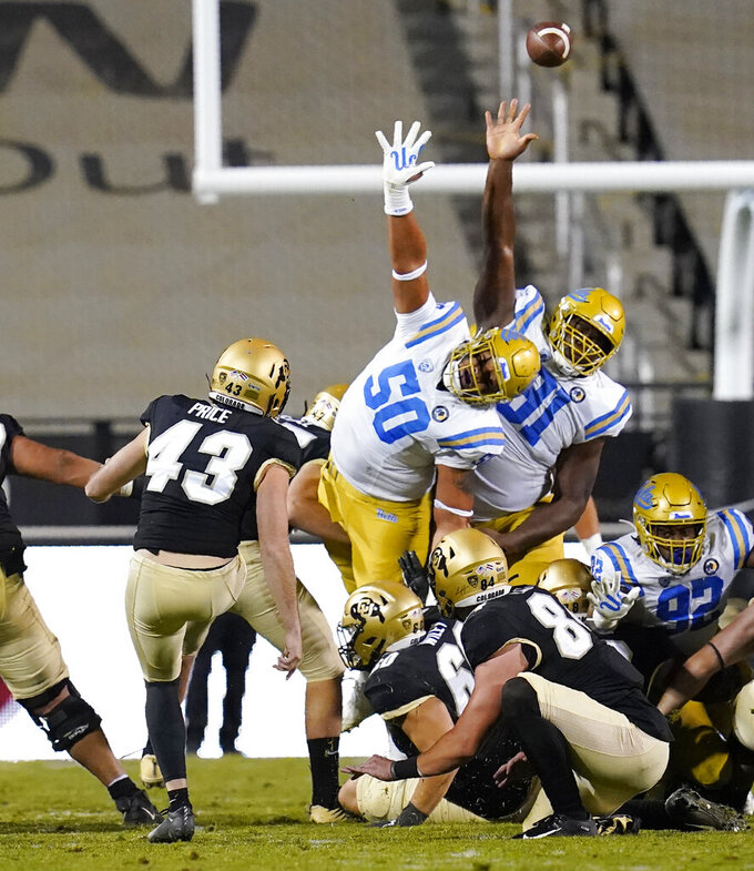 Colorado placekicker Evan Price, front left, and his holder, Matt Lynch, front right, watch as Price's field goal-attempt sails over UCLA special teams players Tyler Manoa, center, and Hudson Habermehl in the second half of an NCAA college football game Saturday, Nov. 7, 2020, in Boulder, Colo. (AP Photo/David Zalubowski)