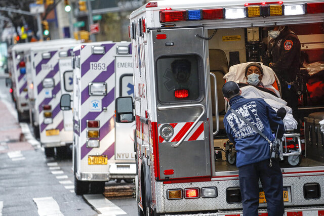 FILE - In this April 13, 2020, file photo, a patient arrives in an ambulance cared for by medical workers wearing personal protective equipment due to COVID-19 concerns outside NYU Langone Medical Center, in New York. The coronavirus has breathed fresh life into old conspiracy theories and inspired a mishmash of new ones, with a cast of villains that includes Bill Gates, 5G wireless technology, the United Nations and President Donald Trump's political foes. The baseless claims spreading on social media also feature videos taken outside hospitals treating COVID-19 patients. (AP Photo/John Minchillo, File)