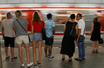 Passengers stand on a platform as a subway train arrives at a station in Prague, Czech Republic, Tuesday, Aug. 7, 2018. Two participants in a travel competition