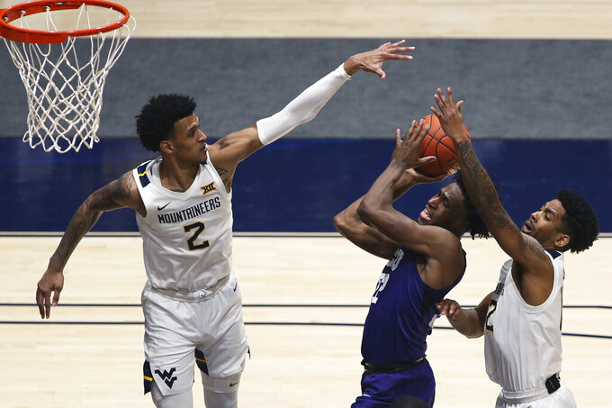 Texas Christian guard RJ Nembhard (22) shoots while defended by West Virginia forward Jalen Bridges (2) and guard Taz Sherman (12) during the second half of an NCAA college basketball game Thursday, March 4, 2021, in Morgantown, W.Va. (AP Photo/Kathleen Batten)