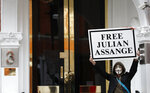 A demonstrator holds up a 'Free Assange' placard outside the front entrance of the Ecuadorian Embassy where Wikileaks founder Julian Assange has been holed out since 2012, in London, Friday, April 5, 2019. A senior Ecuadorian official said no decision has been made to expel Julian Assange from the country's London embassy despite tweets from Wikileaks that sources had told it he could be kicked out within