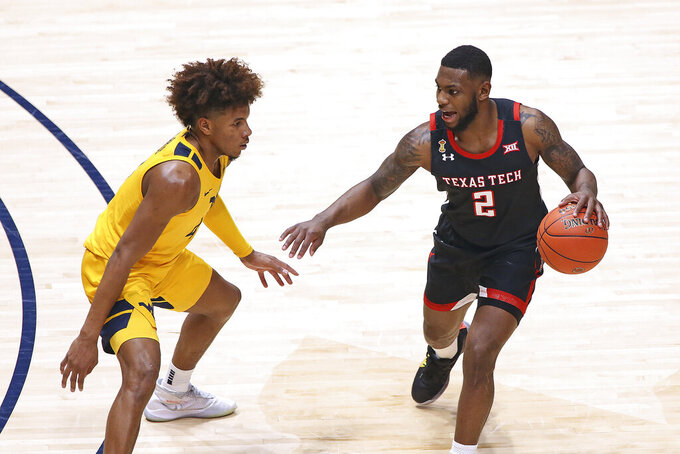 Texas Tech guard Jamarius Burton (2) is defended by West Virginia guard Miles McBride (4) during the second half of an NCAA college basketball game Monday, Jan. 25, 2021, in Morgantown, W.Va. (AP Photo/Kathleen Batten)