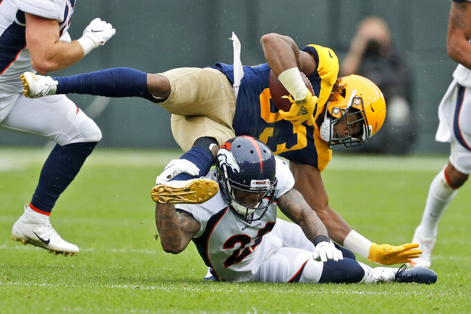 Green Bay Packers running back Aaron Jones, top, falls over Denver Broncos defensive back Kareem Jackson during the first half of an NFL football game Sunday, Sept. 22, 2019, in Green Bay, Wis. (AP Photo/Matt Ludtke)