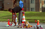 Canfield Green Apartments resident Marcus Hill helps his son Messiah Hill, 2, place a stuffed animal at a newly rebuilt memorial to Michael Brown, Jr. on Thursday, Aug. 8, 2019 in Ferguson, Mo. The site is where Brown was shot and killed by a Ferguson police officer on Aug. 9, 2014.