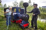 Pavel Chilin, left, and Sergei Terekhov prepare his steam locomotive to run along the miniature personal railway in Ulyanovka village outside St. Petersburg, Russia Sunday, July 19, 2020.  It took Chilin more than 10 years to build the 350-meter-long miniature personal narrow-gauge railway complete with various branches, dead ends, circuit loops, and even three bridges.(AP Photo/Dmitri Lovetsky)