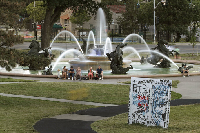 In this photo taken Tuesday, June 23, 2020, people gather at the J.C. Nichols fountain in Kansas City, Mo. The city's board of parks and recreation is considering a proposal to remove the J.C. Nichols name from the fountain and a nearby street as they address racial concerns about the influential local developer. Nichols developed some of the area's most desirable neighborhoods as well as the city's County Club Plaza shopping district in the early 1900's but excluded Blacks, Jews and other minorities using deed restrictions on his properties. (AP Photo/Charlie Riedel)