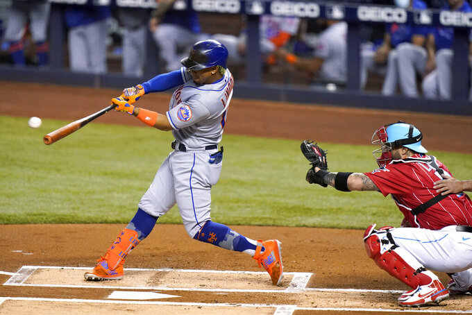 New York Mets' Francisco Lindor hits a double next to Miami Marlins catcher Sandy Leon durning the first inning of a baseball game Friday, May 21, 2021, in Miami. (AP Photo/Lynne Sladky)