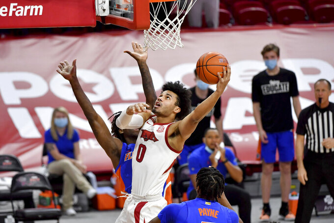 Arkansas forward Justin Smith (0) drives to the hoop against Florida during the first half of an NCAA college basketball game in Fayetteville, Ark. Tuesday, Feb. 16, 2021. (AP Photo/Michael Woods)