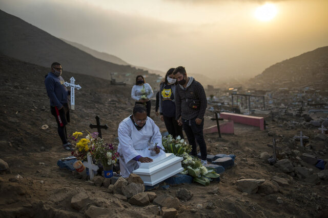 Brother Ronald Marin, a 30-year-old layworker from Venezuela, prays over the coffin of Keizer Quinones and Sarai Araujo's unborn daughter, at a burial service in the Martires 19 de Julio cemetery in Comas, on the outskirts of Lima, Peru, Tuesday, July 21, 2020. Marin is one of the few Catholic Church representatives who administers funerals in the cemetery far from the capital's center that looks like a miniature city wedged between two desert hills. (AP Photo/Rodrigo Abd)