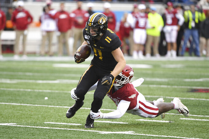 Missouri receiver Barrett Banister (11) is tackled by Arkansas defender Joe Foucha during the first half of an NCAA college football game, Friday, Nov. 29, 2019, in Little Rock, Ark. (AP Photo/Michael Woods)