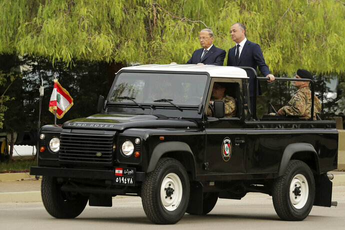 Lebanese President Michel Aoun, left, and Defense Minister Elias Bou Saab, right, stand on a military vehicle before they review Lebanese soldier units during a military parade to mark the 76th anniversary of Lebanon's independence from France at the Lebanese Defense Ministry, in Yarzeh near Beirut, Lebanon, Friday, Nov. 22, 2019. Lebanon's top politicians attended Friday a military parade on the country's 76th Independence Day, appearing for the first time since the government resigned amid nationwide protests now in their second month. (AP Photo/Hassan Ammar)
