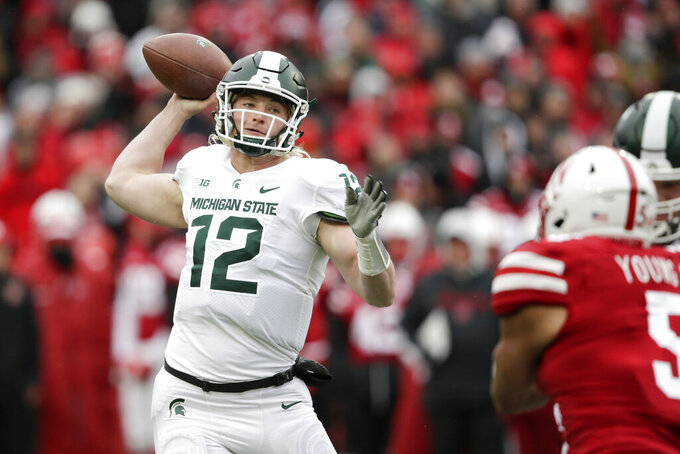 FILE - In this Saturday, Nov. 17, 2018 file photo, Michigan State quarterback Rocky Lombardi (12) throws a pass in front of Nebraska linebacker Dedrick Young II (5) during the first half of an NCAA college football game in Lincoln, Neb. Mel Tucker's success in his first season as Michigan State's coach may be determined in large part by who is playing quarterback. Lombardi made three starts at quarterback in 2018 as a redshirt freshman, and he threw for 173 yards and a touchdown in a win over Rutgers that year. (AP Photo/Nati Harnik, File)