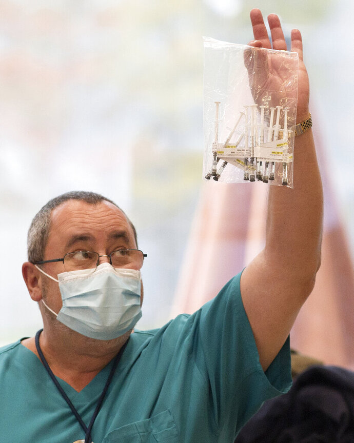 Mark Calkins, with the Southeast Louisiana Veterans Health Care System, holds up a bag containing the first 10 syringes containing Pfizer Inc.'s coronavirus vaccine before it is administered to the staff in New Orleans, Monday, Dec. 14, 2020. (Max Becherer/The Advocate via AP)
