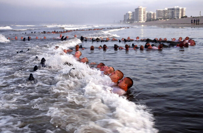 """FILE - In this May 4, 2020 photo provided by the U.S. Navy, SEAL candidates participating in """"surf immersion"""" during Basic Underwater Demolition/SEAL (BUD/S) training at the Naval Special Warfare (NSW) Center in Coronado, Calif. For the first time, a female sailor has successfully completed the grueling 37—week training course to become a Naval Special Warfare combatant-craft crewman — the boat operators that transport Navy SEALs and conduct their own missions at sea. Navy officials said they would not identify the woman, who completed the final phases of training and graduated Thursday. She was one of 17 sailors to receive their pins during the ceremony.  (MC1 Anthony Walker/U.S. Navy via AP)"""
