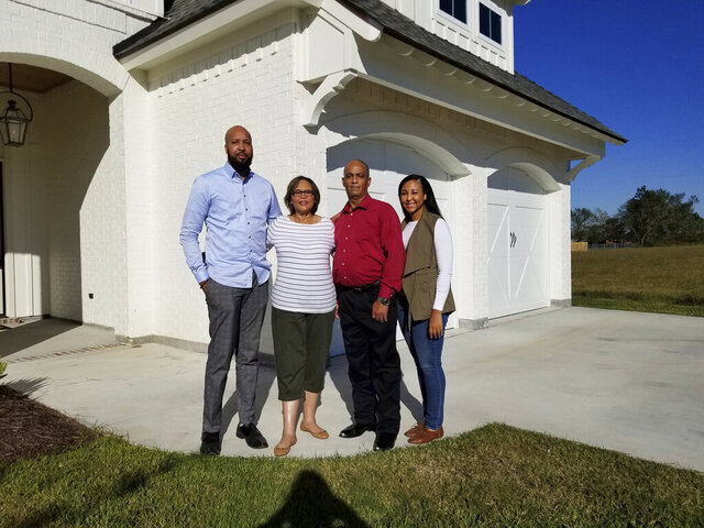 St. Jude Dream Home Giveaway winners Mildred and Joseph Jack, center, check out their new house with their children, Joseph Jack Jr., left, and Rosalyn Jack, right, Wednesday, Aug. 19, 2020 in Lake Charles, La. Mildred Jack, the 2020 St. Jude dream home winner didn't hear her name announced on KPLC-TV Sept. 20. She was in bed recovering from the coronavirus. (Rita LeBleu/American Press via AP)