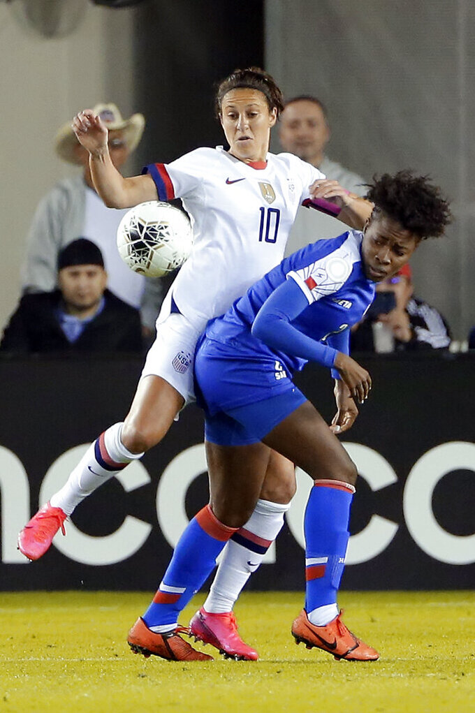 United States forward Carli Lloyd (10) and Haiti defender Soveline Beaubrun, right, collide as they go for the ball during the first half of a women's Olympic qualifying soccer match Tuesday, Jan. 28, 2020, in Houston. (AP Photo/Michael Wyke)