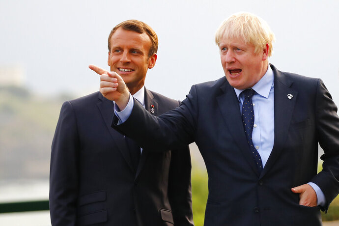 French President Emmanuel Macron, left, welcomes Britain's Prime Minister Boris Johnson at the Biarritz lighthouse, southwestern France, ahead of a working dinner Saturday, Aug.24, 2019. Shadowed by the threat of global recession, a U.S. trade war with China and the possibility of one against Europe, the posturing by leaders of the G-7 rich democracies began well before they stood together for a summit photo. (AP Photo/Francois Mori, Pool)