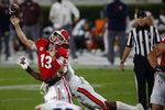 Georgia quarterback Stetson Bennett (13) is hit by Auburn linebacker Zakoby McClain during the first half of an NCAA college football game in Athens, Ga., Saturday, Oct. 3, 2020. (Joshua L. Jones/Athens Banner-Herald via AP)