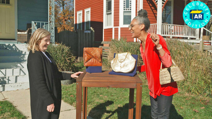 "This image released by WGBH-TV shows Katy Kane, left, as she appraises celebrity chef Carla Hall's vintage purse collection in an episode of ""Antiques Roadshow Celebrity Edition,"" airing May 10 on PBS. (WGBH/PBS via AP)"