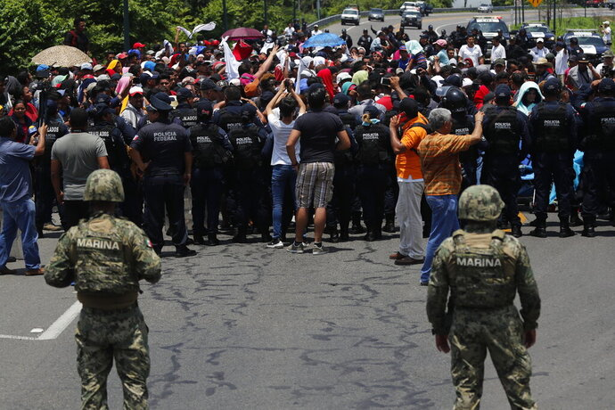 FILE - In this June 5, 2019 file photo, Mexican authorities stop a migrant caravan that had earlier crossed the Mexico - Guatemala border, near Metapa, Chiapas state, Mexico. Mexico said in Friday, Sept. 5, that it has complied with a 90-day deadline from the U.S. to reduce the flow of migrants through its territory, but activists say Mexico's crackdown has only forced migrants into greater desperation and more illicit, dangerous routes. (AP Photo/Marco Ugarte, File)