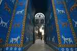 People walk near Ishtar Gate the archaeological site of Babylon, Iraq, Friday, July 5, 2019. Iraq on Friday celebrated the UNESCO World Heritage Committee's decision to name the historic city of Babylon a World Heritage Site in a vote held in Azerbaijan's capital, years after Baghdad began campaigning for the site to be added to the list. (AP Photo/Anmar Khalil)
