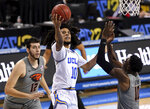 Tyger Campbell, center,  of UCLA, drives to the basket against the Oregon State defense in the first half of an NCAA college basketball game Saturday, Jan. 30, 2021, in Los Angeles. (Keith Birmingham/The Orange County Register via AP)