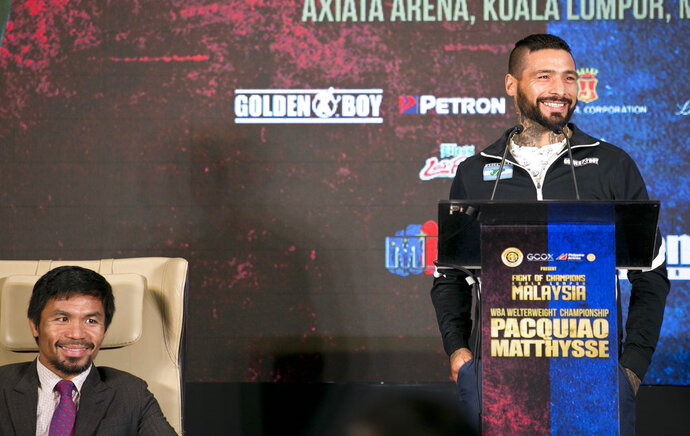 Argentine WBA welterweight champion Lucas Matthysse speaks as Philippine senator and boxing hero Manny Pacquiao smiles during a press conference in Kuala Lumpur, Malaysia, Thursday, July 12, 2018. Matthysse and Pacquiao were scheduled to fight on July 15, for the World Boxing Association welterweight title in Malaysia. (AP Photo/Yam G-Jun)