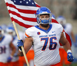 Boise State offensive lineman Ezra Cleveland carries out a United States flag as the team takes the field to face Air Force in an NCAA college football game Saturday, Oct. 27, 2018, at Air Force Academy, Colo. (AP Photo/David Zalubowski)