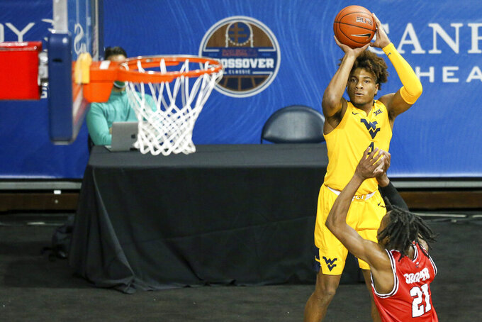 West Virginia guard Miles McBride (4) shoots a 3-pointer over Western Kentucky guard Kenny Cooper (21) during the first half of an NCAA college basketball game Friday, Nov. 27, 2020, in SIoux Falls, S.D. (AP Photo/Josh Jurgens)