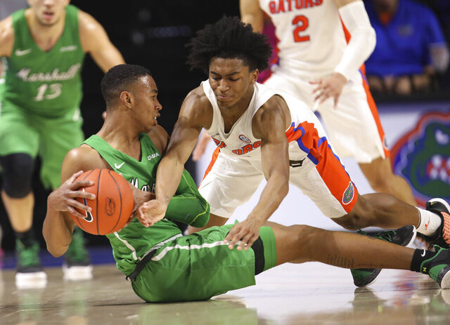 Marshall guard Taevion Kinsey (1) and Florida guard Ques Glover (0) scramble for the ball during the second half of an NCAA college basketball game Friday, Nov. 29, 2019, in Gainesville, Fla. (AP Photo/Matt Stamey)