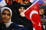 Women react as they listen to Turkey's President Recep Tayyip Erdogan addressing the supporters of his ruling Justice and Development Party, AKP, at a rally in Istanbul, late Tuesday, March 19, 2019, ahead of local elections scheduled for March 31, 2019. An image of AKP's mayoral candidate for Istanbul, Binali Yildirim, is seen in the background. (AP Photo/Emrah Gurel)