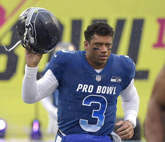 "FILE - In this Jan. 27, 2019, file photo, NFC quarterback Russell Wilson of the Seattle Seahawks runs onto the field during player introductions before the NFL Pro Bowl football game against the AFC in Orlando, Fla. Wilson posted a video to social media early Tuesday, Apriil 16, 2019, saying, ""Seattle, we got a deal,"" shortly after a reported midnight deadline for the Seahawks and their star quarterback to agree on a contract extension. Wilson's current $87.6 million, four-year deal was signed at the beginning of training camp in 2015 and was set to expire after next season. (AP Photo/Phelan M. Ebenhack, File)"