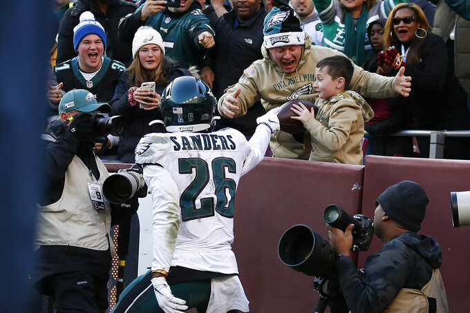 Philadelphia Eagles running back Miles Sanders (26) gives the football to a young fan after scoring a touchdown in the second half of an NFL football game against the Washington Redskins, Sunday, Dec. 15, 2019, in Landover, Md. (AP Photo/Alex Brandon)