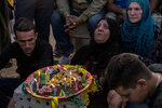 Relatives mourn during a funeral of a Syrian Democratic Forces fighter in the Syrian town of Qamishli, Saturday, Oct. 12, 2019, Turkey's military says it has captured a key Syrian border town Ras al-Ayn under heavy bombardment in its most significant gain as its offensive against Kurdish fighters presses into its fourth day. (AP Photo/Baderkhan Ahmad)