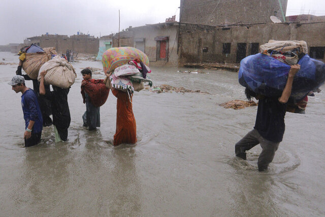 Local residents carry salvaged belongings as they wade through a flooded area during a heavy monsoon rain in Yar Mohammad village near Karachi, Pakistan, Thursday, Aug. 27, 2020. Pakistan's military said it will deploy rescue helicopters to Karachi to transport some 200 families to safety after canal waters flooded the city amid monsoon rains. (AP Photo/Fareed Khan)