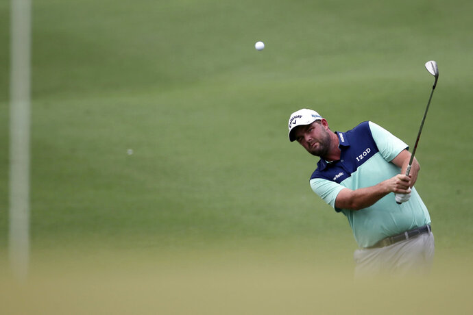 Marc Leishman of Australia follows his shot on the seventh hole during round two of the CIMB Classic golf tournament at Tournament Players Club (TPC) in Kuala Lumpur, Malaysia, Friday, Oct. 12, 2018. (AP Photo/Vincent Phoon)
