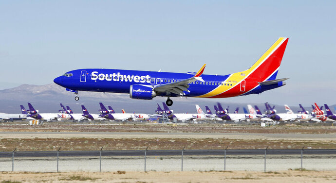 FILE - In this March 23, 2019 file photo a Southwest Airlines Boeing 737 Max aircraft lands at the Southern California Logistics Airport in the high desert town of Victorville, Calif. Southwest said Thursday, Oct. 17, that it will keep its Boeing 737 Max jets out of its schedule until Feb. 8, about a month longer than previously planned. (AP Photo/Matt Hartman, File)