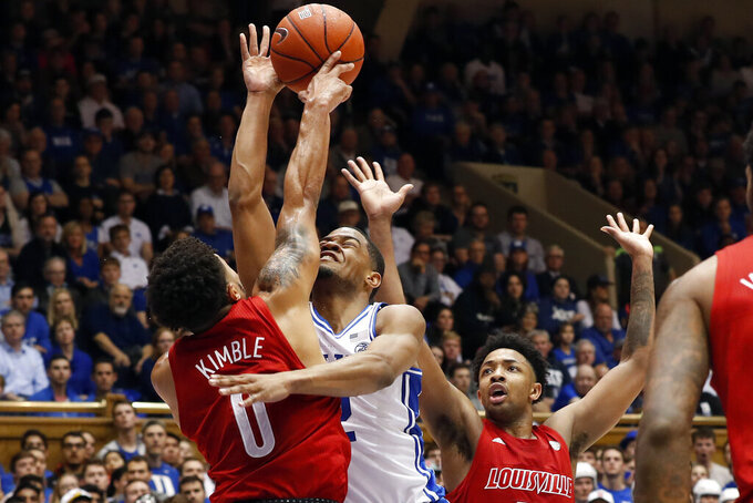 Duke guard Cassius Stanley drives to the basket while Louisville guards Lamarr Kimble (0) and David Johnson, right, defend during the second half of an NCAA college basketball game in Durham, N.C., Saturday, Jan. 18, 2020. Louisville won 79-73. (AP Photo/Gerry Broome)