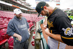 Pittsburgh Pirates' relief pitcher Connor Overton (41) stands in the rain to sign an autograph for Kurt Moody, of Houston, Texas, after a baseball game against the Cincinnati Reds was postponed in Cincinnati, Wednesday, Sept 22, 2021. (AP Photo/Bryan Woolston)