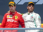 Mercedes driver Lewis Hamilton, right, of Britain, consoles Ferrari driver Sebastian Vettel, of Germany, after Hamilton won the Formula One Canadian Grand Prix auto race Sunday, June 9, 2019 in Montreal. Vettel finished first but was assessed a penalty to end up in second place. (Ryan Remiorz/The Canadian Press via AP)