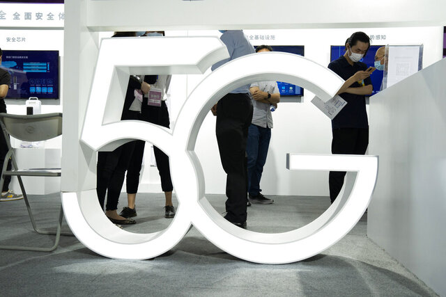 """FILE - In this Sept. 17, 2020 file photo, visitors wearing mask to protect from the coronavirus walk past a 5G sign at the China Beijing International High Tech Expo in Beijing, China. A much-hyped network upgrade called """"5G"""" means different things to different people. To industry proponents, it's the next huge innovation in wireless internet. To the U.S. government, it's the backbone technology of a future that America will wrestle with China to control.  (AP Photo/Ng Han Guan, File)"""