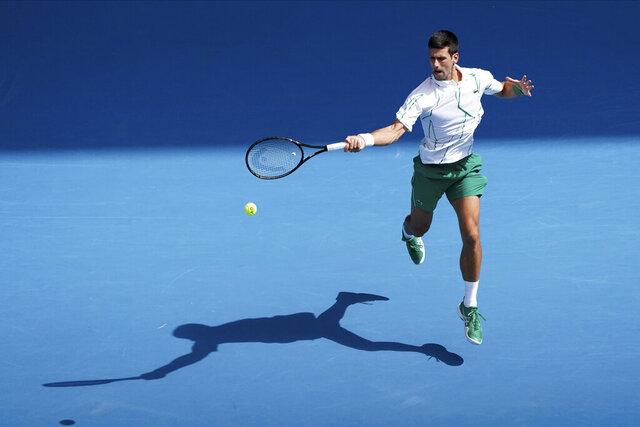 Serbia's Novak Djokovic returns a shot against Japan's Yoshihito Nishioka in their third round singles match at the Australian Open tennis championship in Melbourne, Australia, Friday, Jan. 24, 2020. (AP Photo/Lee Jin-man)