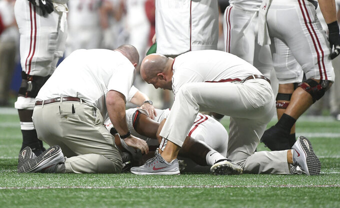FILE - In this Dec. 1, 2018, file photo, Alabama quarterback Tua Tagovailoa (13) is helped by medical staff during the second half of the Southeastern Conference championship NCAA college football game against Georgia, in Atlanta. More than one-third of college athletic trainers say coaches influence the hiring and firing of their schools' sports-medicine staffs, a finding that counters an NCAA-recommended protocol urging medical staff to make decisions about athlete health independent of coaches and administrators. (AP Photo/John Amis, File)