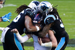Denver Broncos quarterback Drew Lock is tackled by Carolina Panthers defensive end Austin Larkin and safety Tre Boston during the second half of an NFL football game Sunday, Dec. 13, 2020, in Charlotte, N.C. (AP Photo/Gerry Broome)