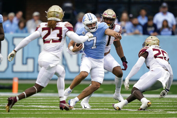 North Carolina quarterback Sam Howell (7) runs with the ball while Florida State defensive back Sidney Williams (23), linebacker Kalen DeLoach (20) and defensive end Jermaine Johnson II, rear, look to tackle him during the first half of an NCAA college football game in Chapel Hill, N.C., Saturday, Oct. 9, 2021. (AP Photo/Gerry Broome)