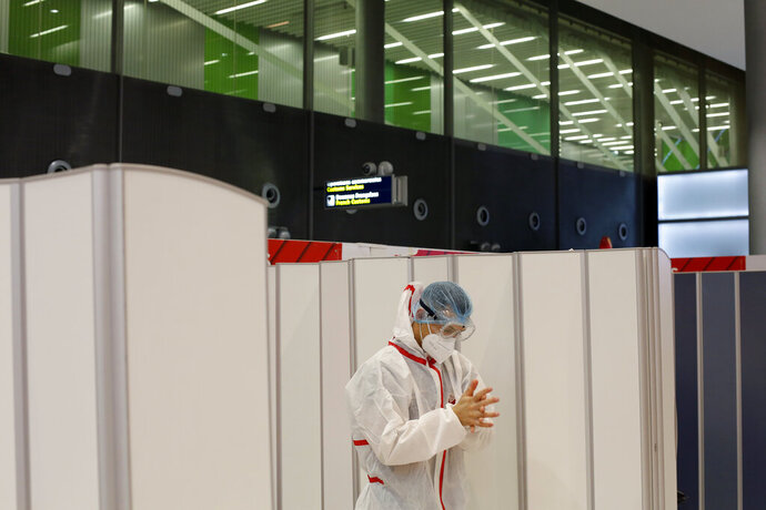 A health worker washes his hands after he collected a nasal swab sample for COVID-19 test, at the Roissy Charles de Gaulle airport, outside Paris, Saturday, Aug. 1, 2020. Travelers entering France from 16 countries where the coronavirus is circulating widely are having to undergo virus tests upon arrival at French airports and ports.(AP Photo/Thibault Camus)