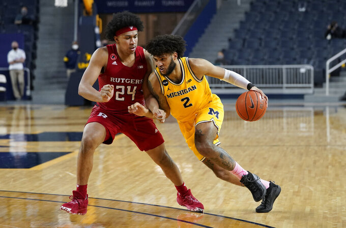 Michigan Wolverines forward Isaiah Livers (2) drives on Rutgers guard Ron Harper Jr. (24) in the second half of an NCAA college basketball game in Ann Arbor, Mich., Thursday, Feb. 18, 2021. (AP Photo/Paul Sancya)