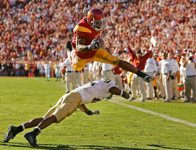 FILE - In this Dec. 3, 2005, file photo, Southern California's Reggie Bush leaps over UCLA defender Marcus Cassel as he rushes 13 yards for a touchdown in the second quarter of their game at the Los Angeles Memorial Coliseum. USC set a record by going 33 straight polls as No. 1 from 2003-05. The Trojans weren't just the best team in college football, they were also arguably the coolest, with the charismatic, laid-back Carroll leading stars like quarterback Matt Leinart and running back Reggie Bush to victory after victory. (AP Photo/Chris Carlson, File)