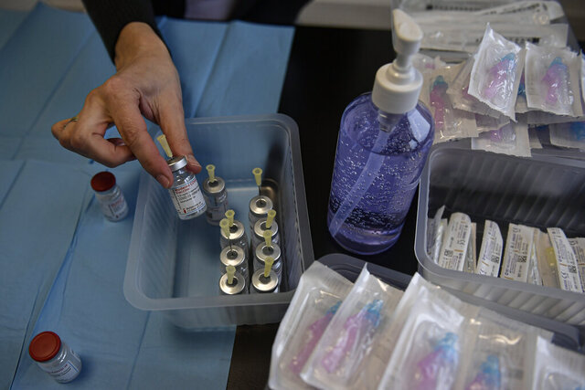A health worker prepares Moderna coronavirus vaccines before vaccinating staff health workers at Clinica Universitaria, in Pamplona, northern Spain, Wednesday, Jan. 20, 2021. (AP Photo/Alvaro Barrientos)